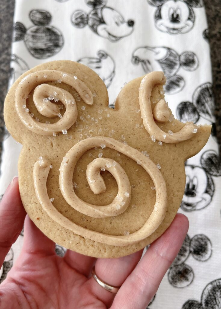 A Mickey Mouse Churro Sugar Cookie with a bite out of the ear.