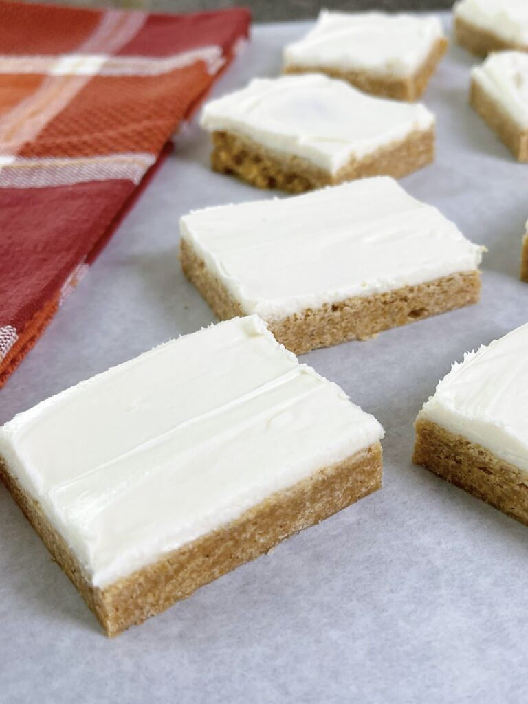 A picture of pumpkin sugar cookie bars with cream cheese frosting.