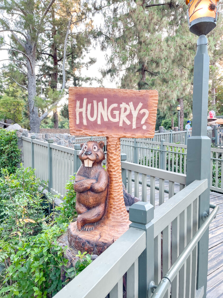 """A sign made of wood that says """"hungry?"""" at Hungry Bear Restaurant in Disneyland."""