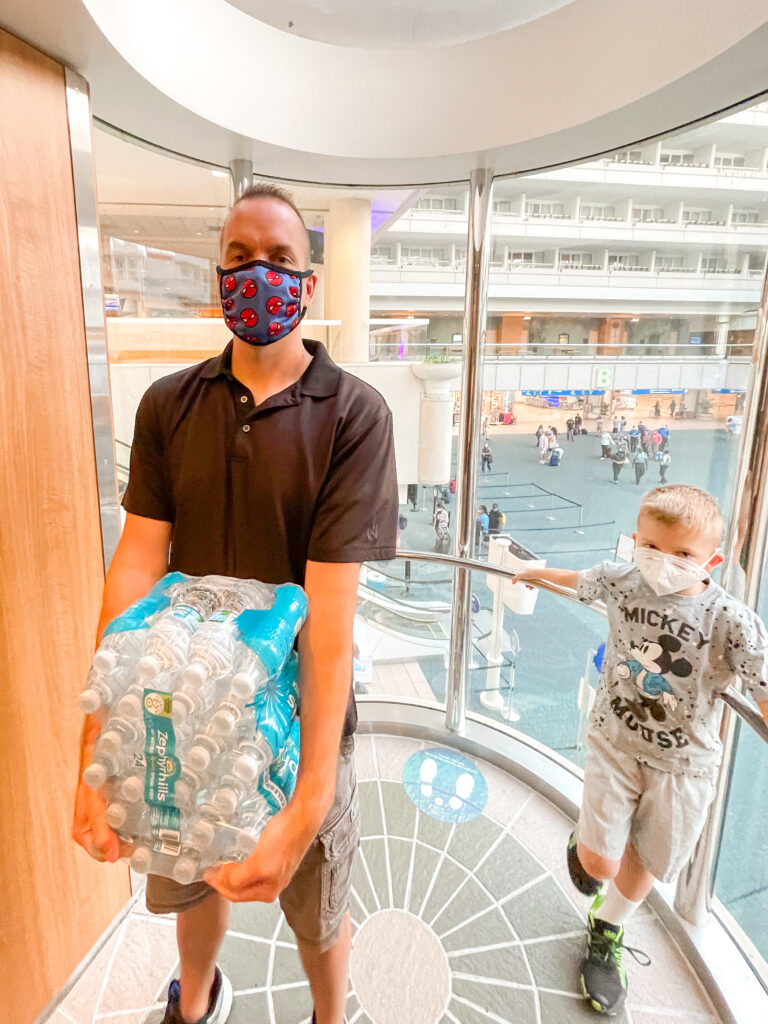 A man and a child holding a case of bottled water to take on a Disney Cruise.