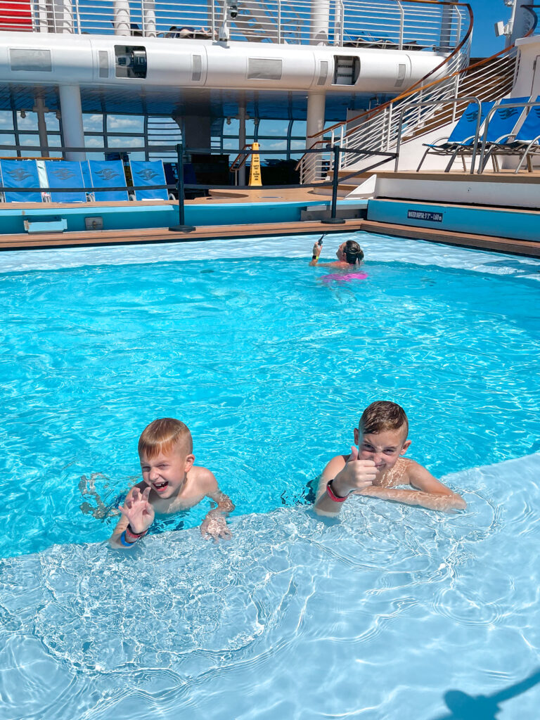 Two kids swimming in a pool on the Disney Dream.