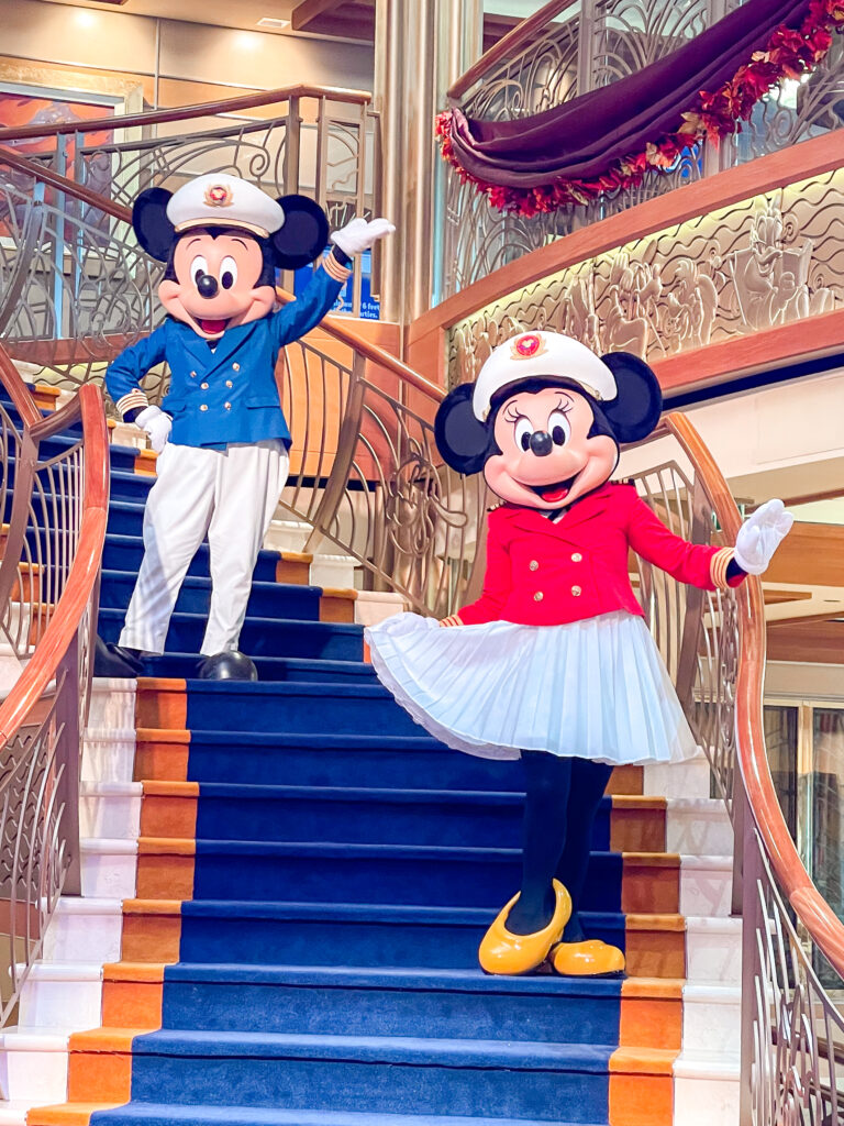 Captain Mickey and Captain Minnie on the stairs in the atrium of the Disney Dream Cruise Ship.
