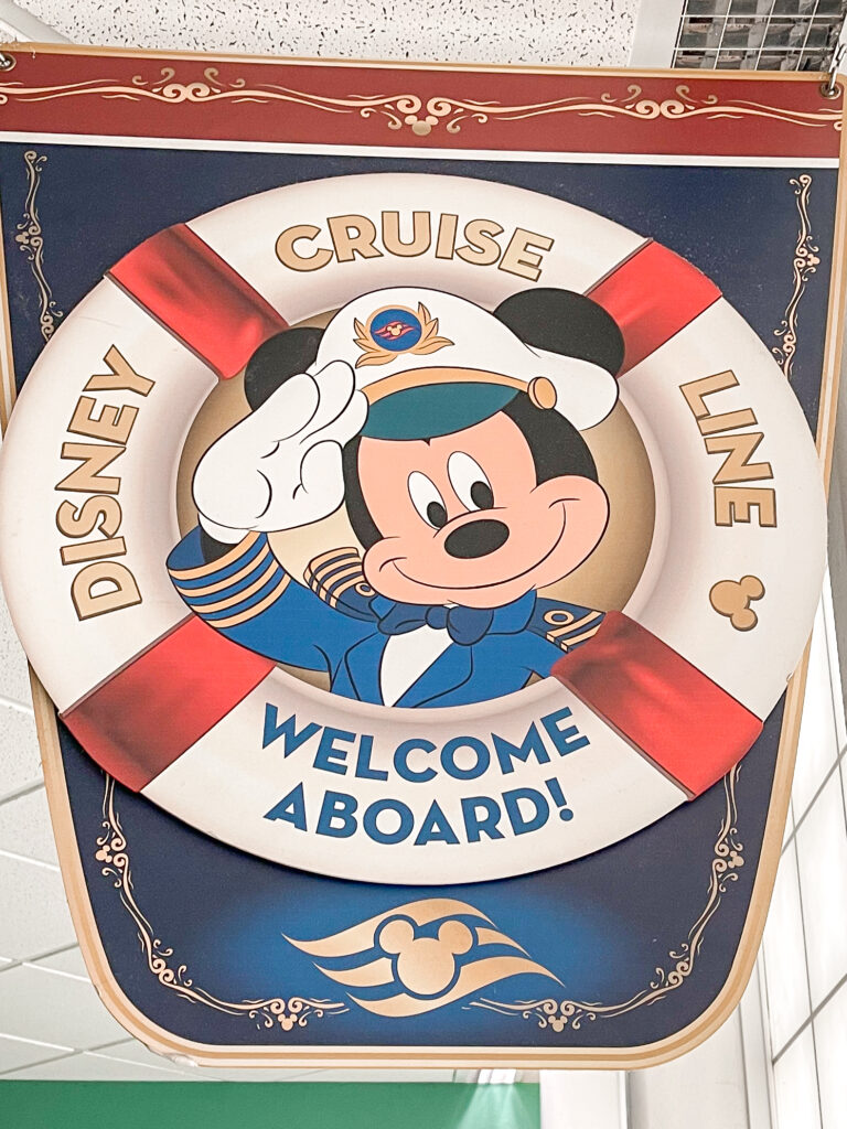 """A sign with a picture of Mickey Mouse in the center of a life preserver that says """"Disney Cruise Line Welcome Aboard!"""""""