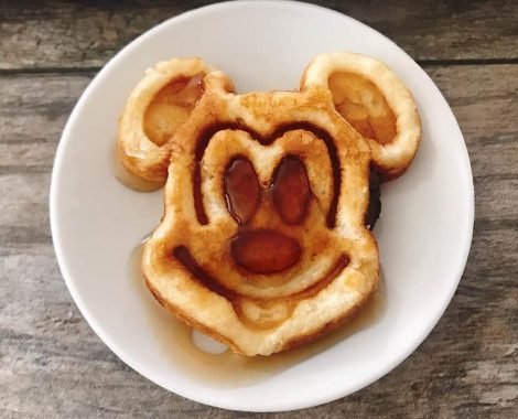 A Mickey Mouse shaped crispy waffle with syrup on a white plate.